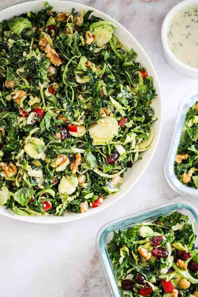 Large white bowl of green salad with two glass meal prep containers filled with salad and a ramekin of tahini dressing.
