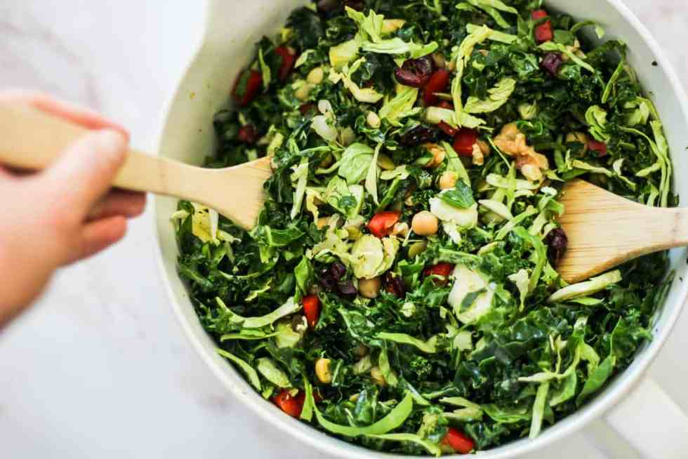 Horizontal image of mixing a green salad with wooden spoons.