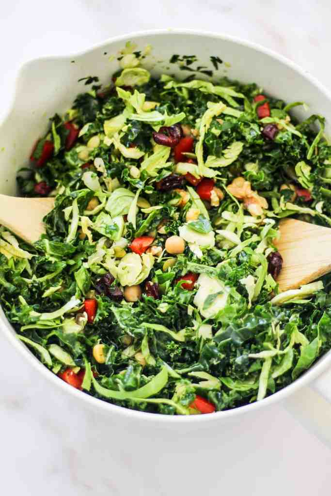 Closeup image of a meal prep kale salad in a large mixing bowl.