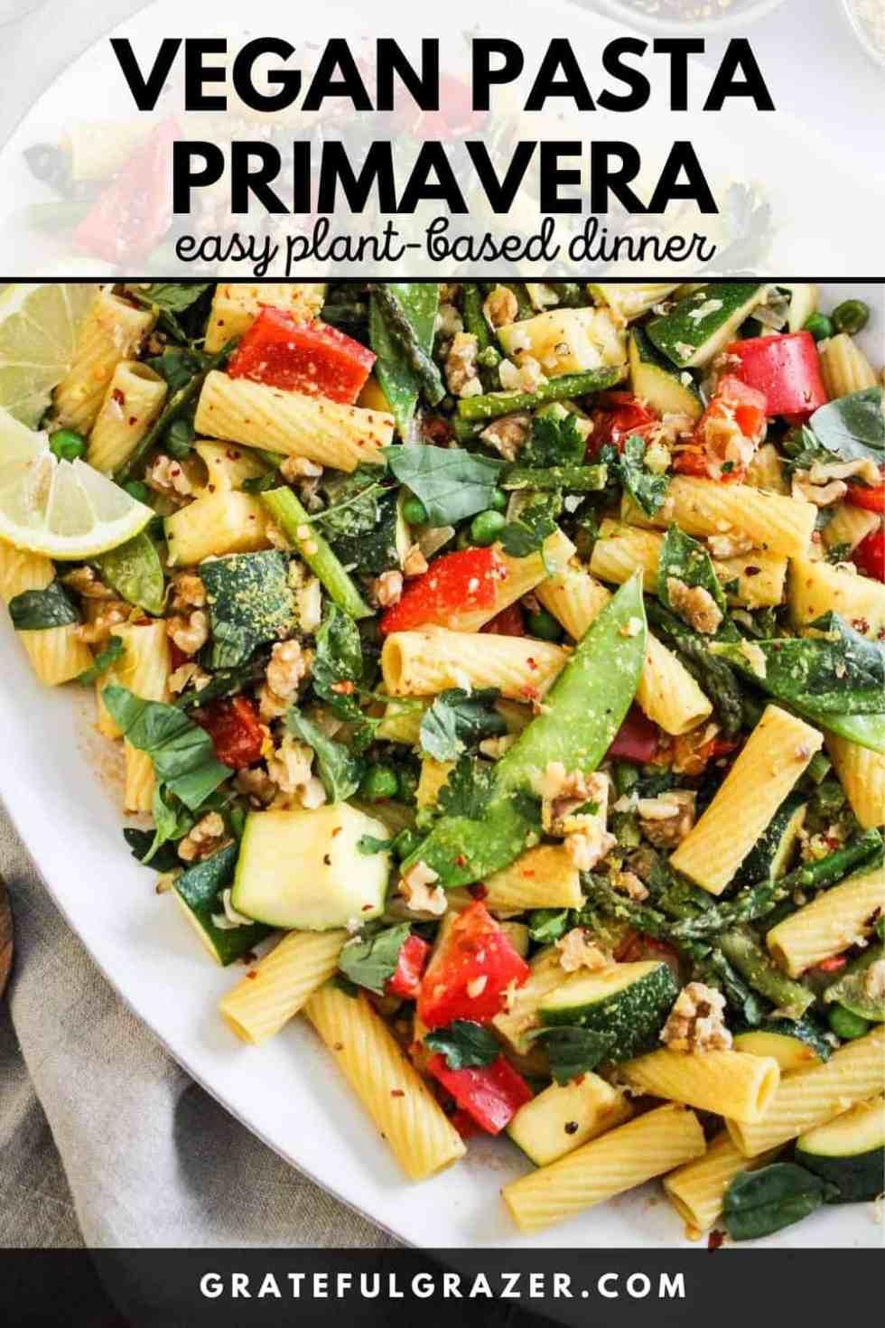 """Vegetable pasta on a white platter with black text reading, """"Vegan Pasta Primavera: easy plant-based dinner; GratefulGrazer.com."""""""