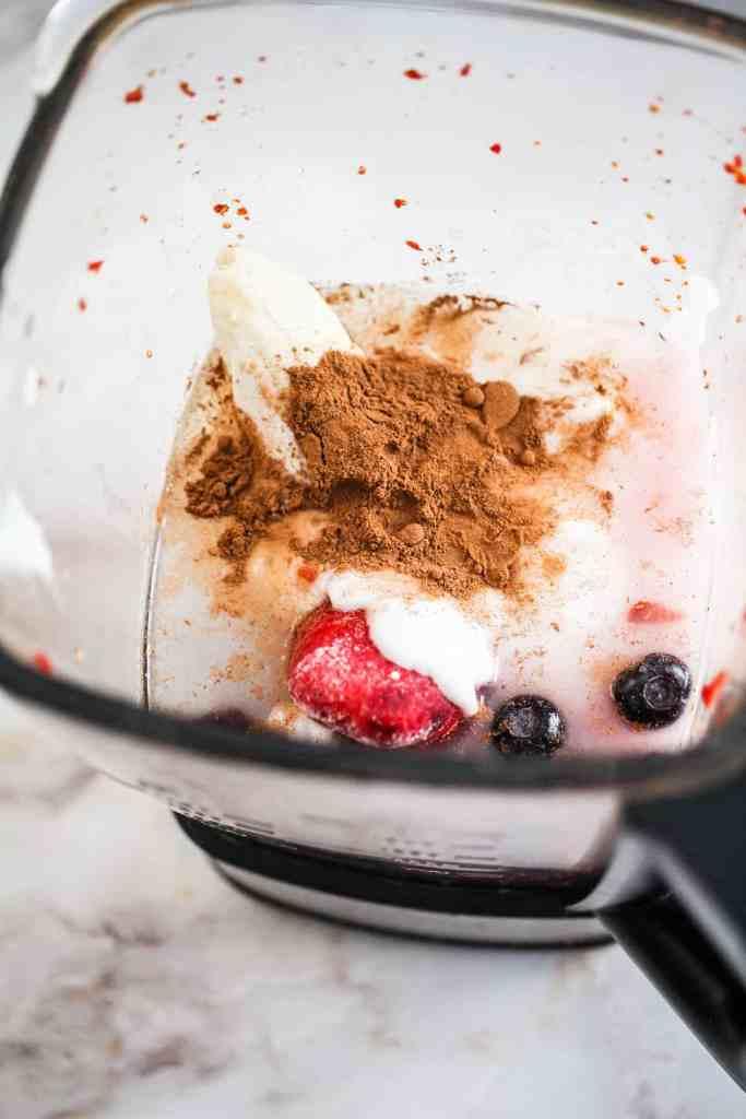 Banana, cinnamon, berries, coconut water, and So Delicious yogurt alternative in a blender.