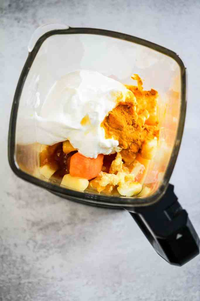 Fruit, yogurt, and spices in a blender.