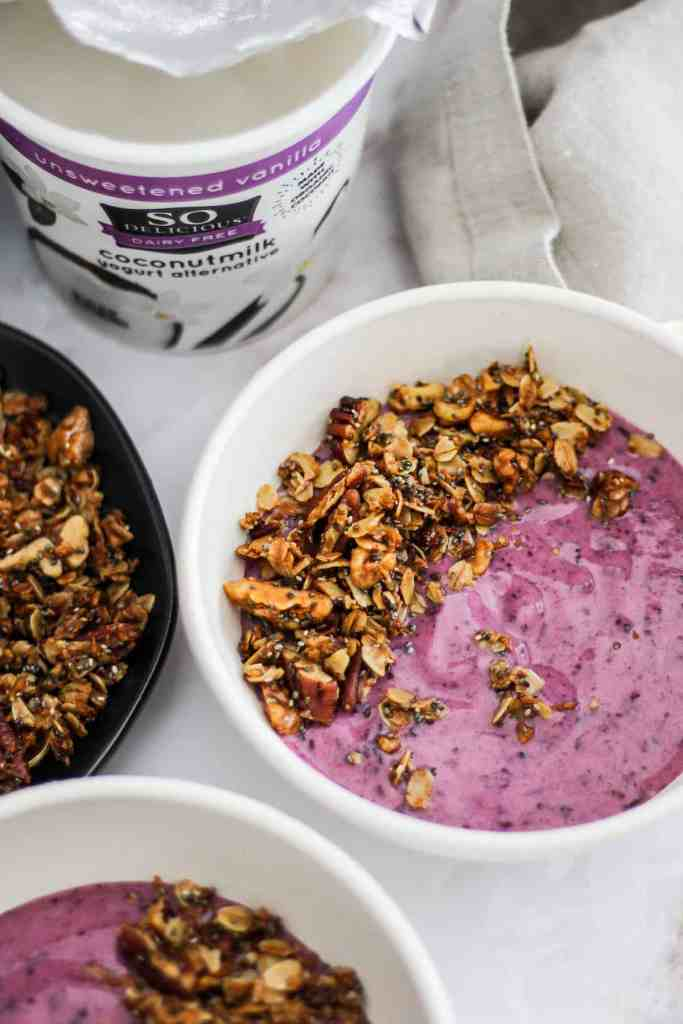 Wild blueberry So Delicious Yogurt Alternative in a white bowl topped with homemade granola.