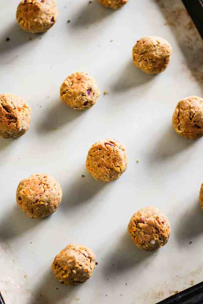 Baked falafel on a baking sheet lined with a silicone baking mat.
