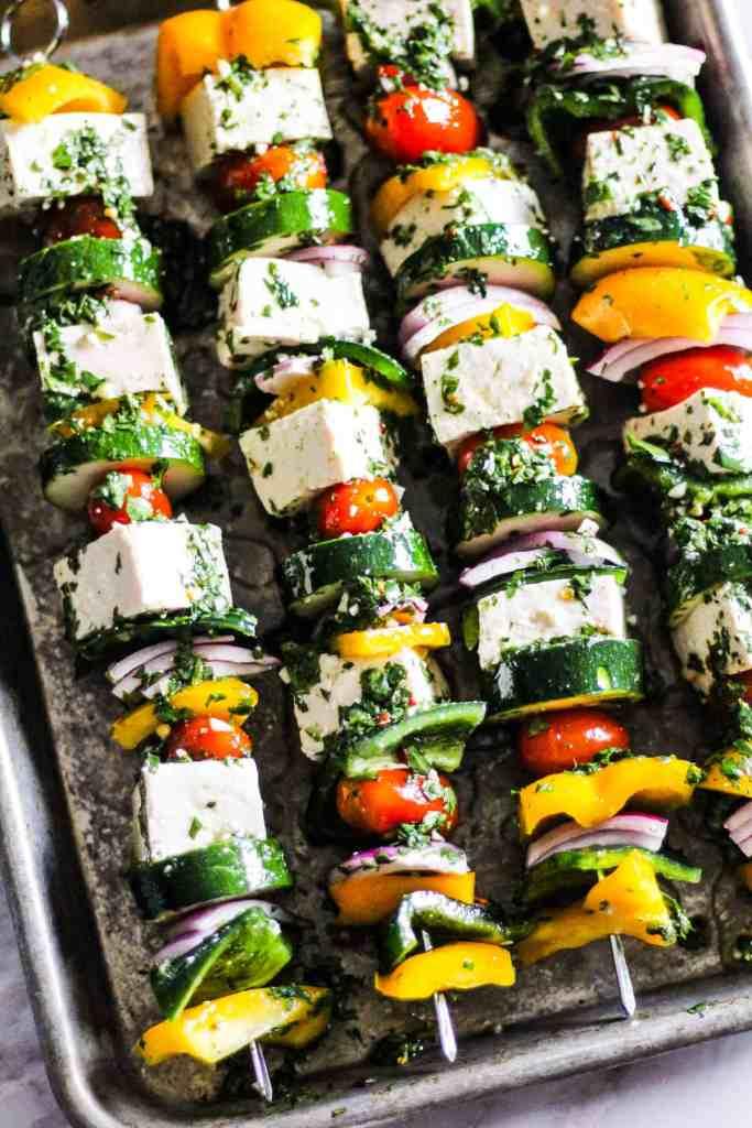 Marinating tofu and vegetable kebabs with chimichurri sauce.