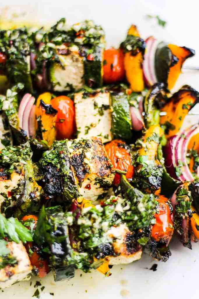 Closeup of grilled tofu and vegetables with chimichurri sauce.