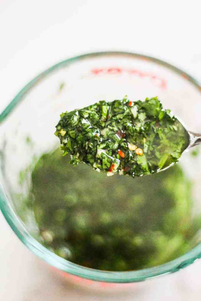 Spoonful of green chimichurri sauce held over a liquid measuring cup.