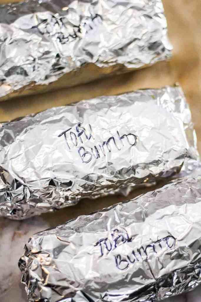 "Burritos wrapped in aluminum foil with the label, ""tofu burrito"" written in black marker."