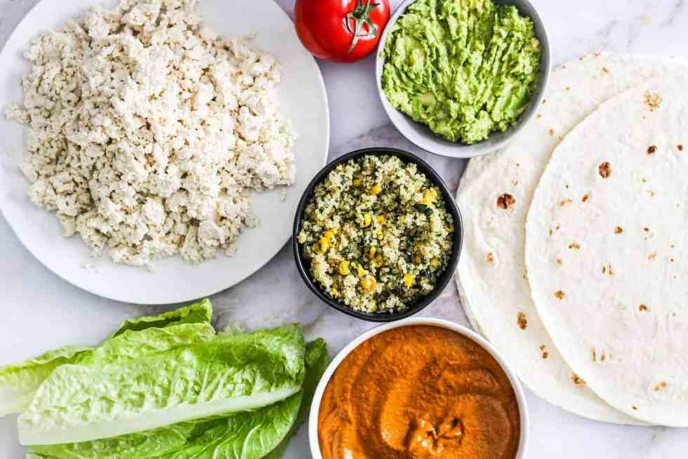 Flatlay photo of burrito ingredients: crumbled tofu, lettuce, quinoa, tomato, avocado, Sofrito sauce, and tortillas.