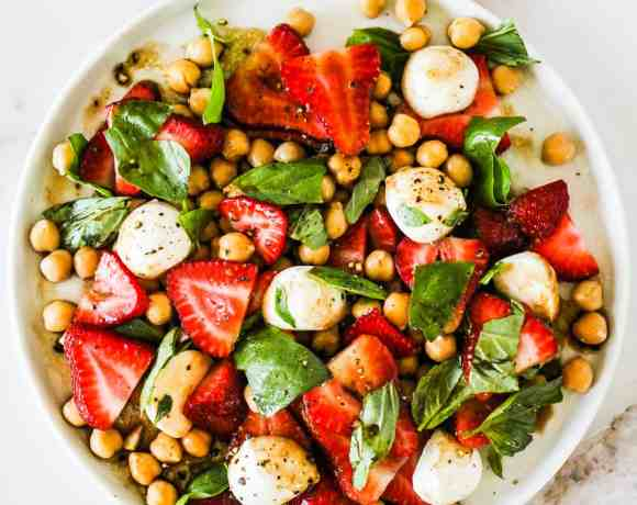 Summer Strawberry Salad with chickpeas, mozzarella, and basil on a white plate.