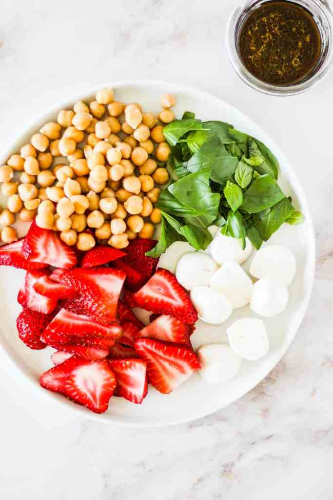 Chickpeas, strawberries, mozzarella, and basil sectioned off on a white plate.