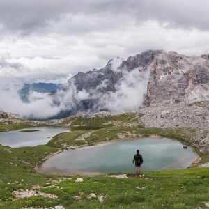 man standing in front of lake with mountains and clouds ahead