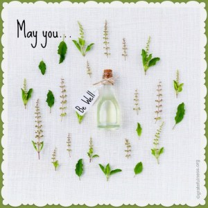 A small bottle on a white linen cloth surrounded by herbs.
