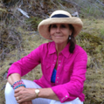 Smiling woman in bright pink shirt and straw hat