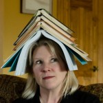 Woman with books stacked on her head.