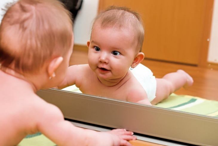 bebelus care se uita in oglinda, bebe, fetita,