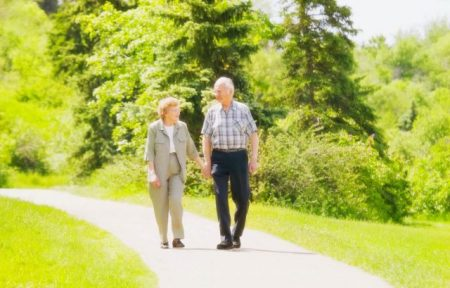 senior couple walking along a sidewalk in a park