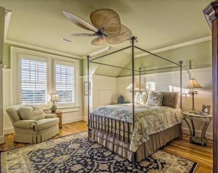 a very tall canopy bed in a well decorated bedroom with a blue rug
