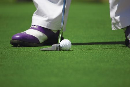 feet of a golfer in purple shoes about to use a putter on a green