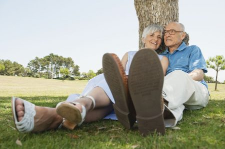two seniors under a tree with a close up of their shoes