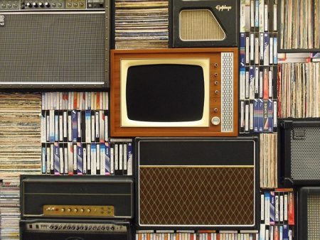 an old fashioned tv surrounded by antique audio equipment