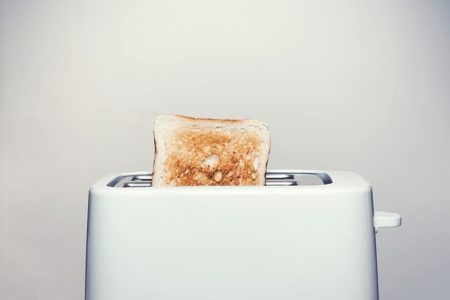 toaster sitting on top of a white toaster on a gray background