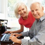 senior man and woman smiling while using a large computer keyboard