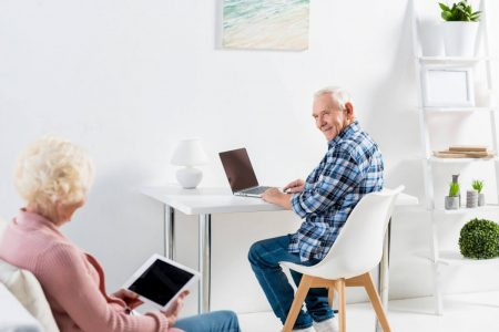 senior man using a laptop while his senior wife uses a tablet