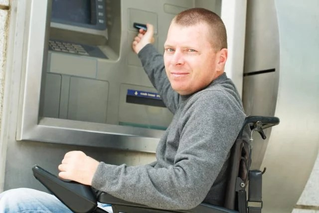 man using a portable power chair at an atm