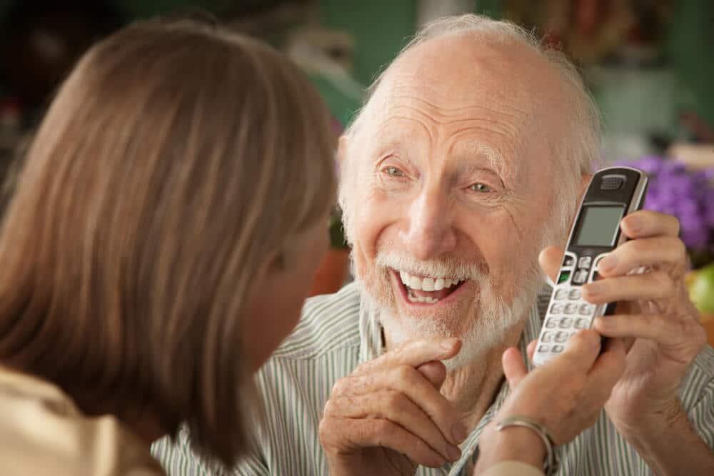 senior man showing his daughter his cordless phone
