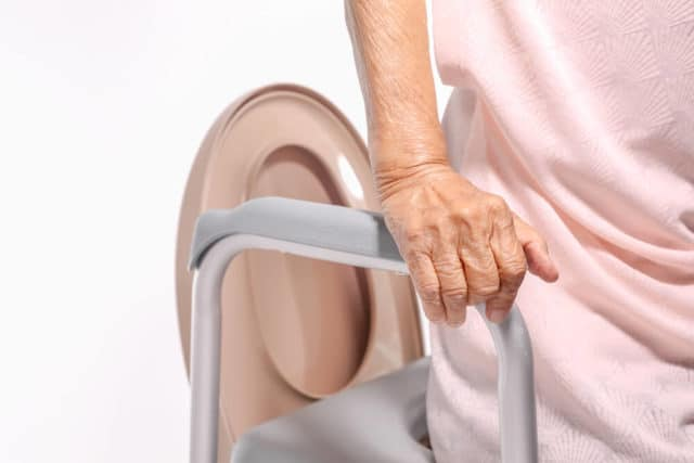 elderly woman getting up from her tall toilet