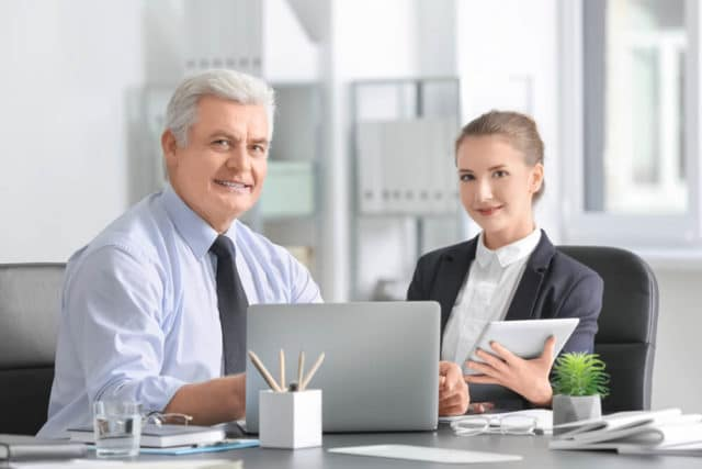 senior man consulting with woman at work