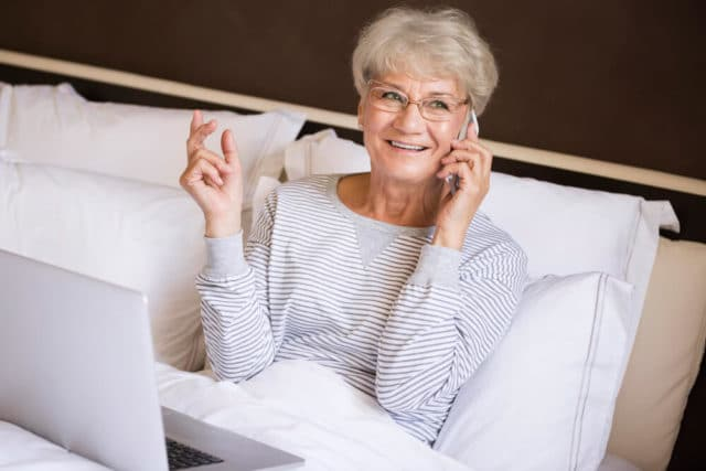 senior woman working in bed with a laptop