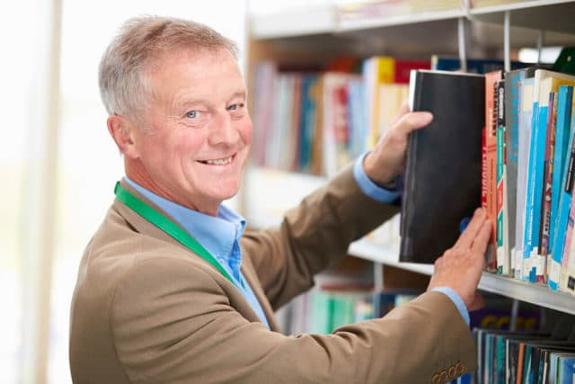 senior man over 60 working his job at the library