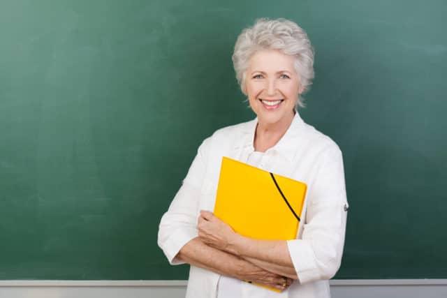 senior woman over 60 teaching a class as her job