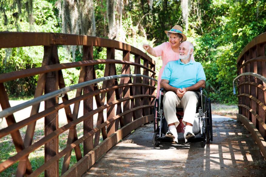 woman pushing husband in a lightweight wheelchair