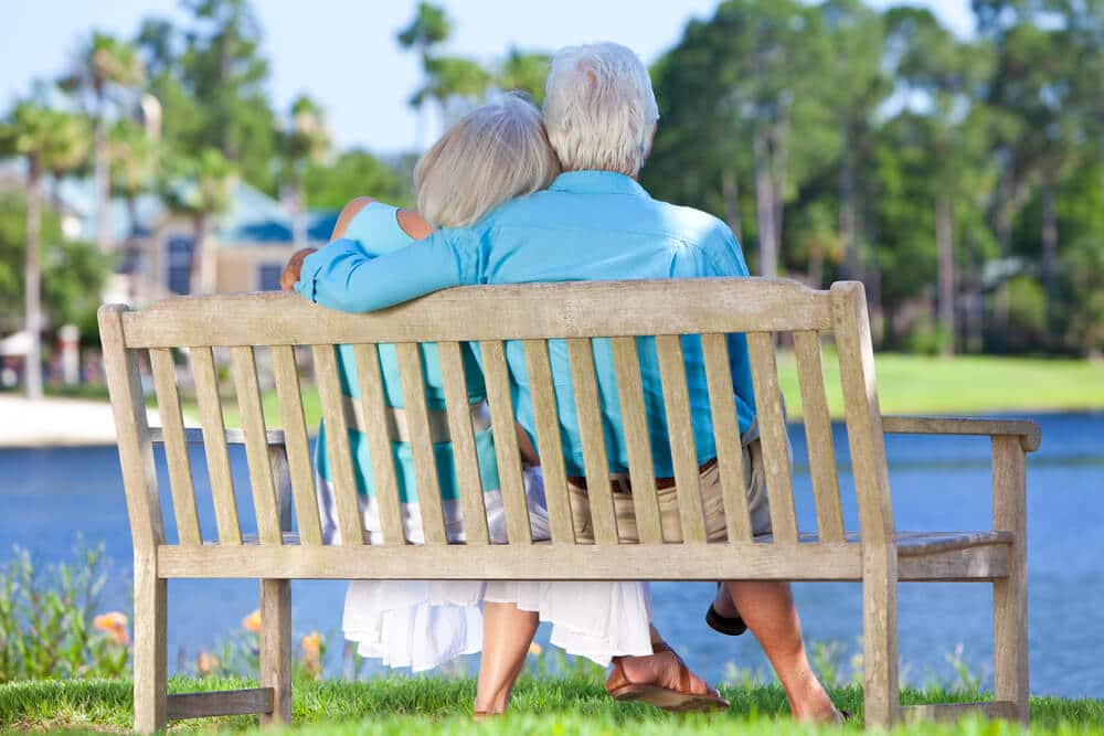 senior couple resting on a bench on vacation