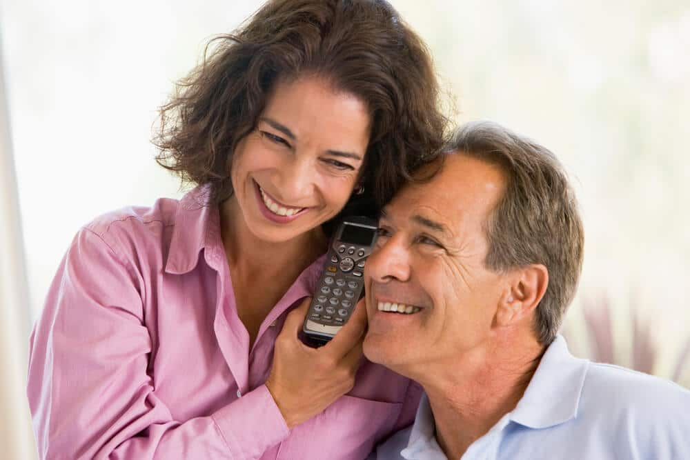 senior couple listening to a message on cordless phone with answering machine