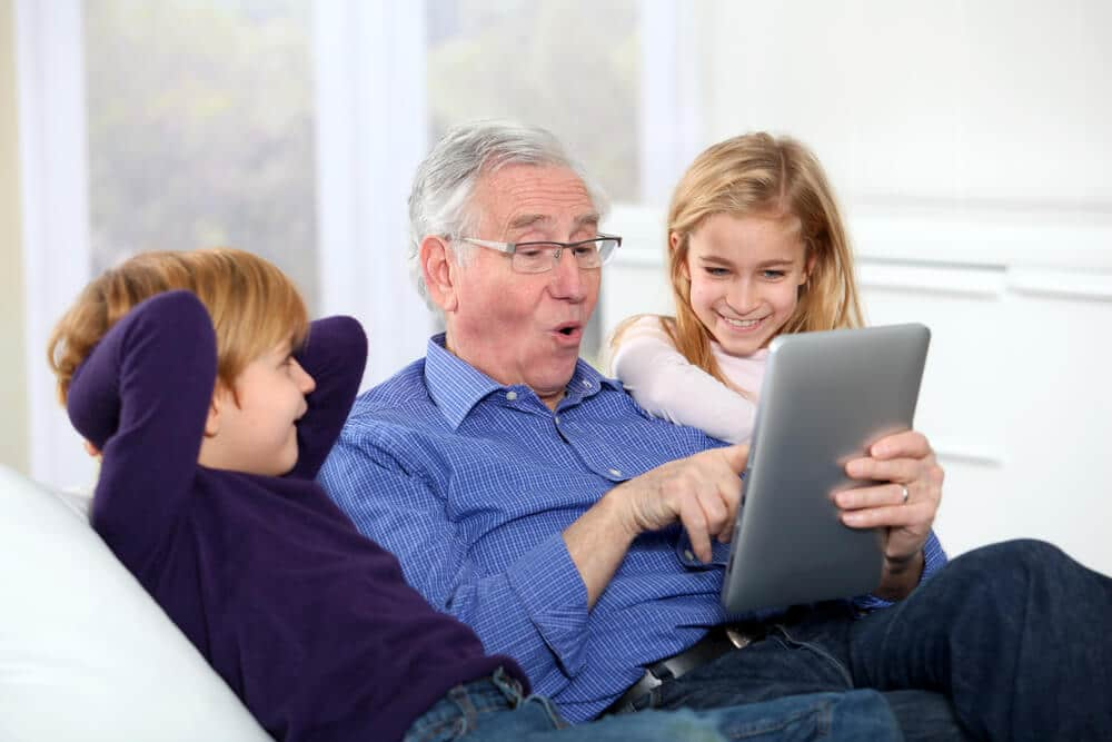senior man using an easy tablet with his grandkids