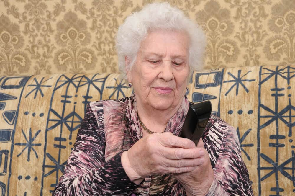 senior woman dialing a simple cordless phone