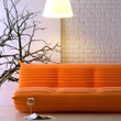 A orange couch with a floor lamp