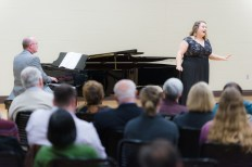 Grace VanHoven sings. A man plays a grand piano behind her, and an audience is seated in front of her.