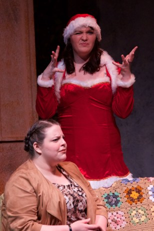 A student actress, dressed in a Christmas outfit, stands next to a seated actress.