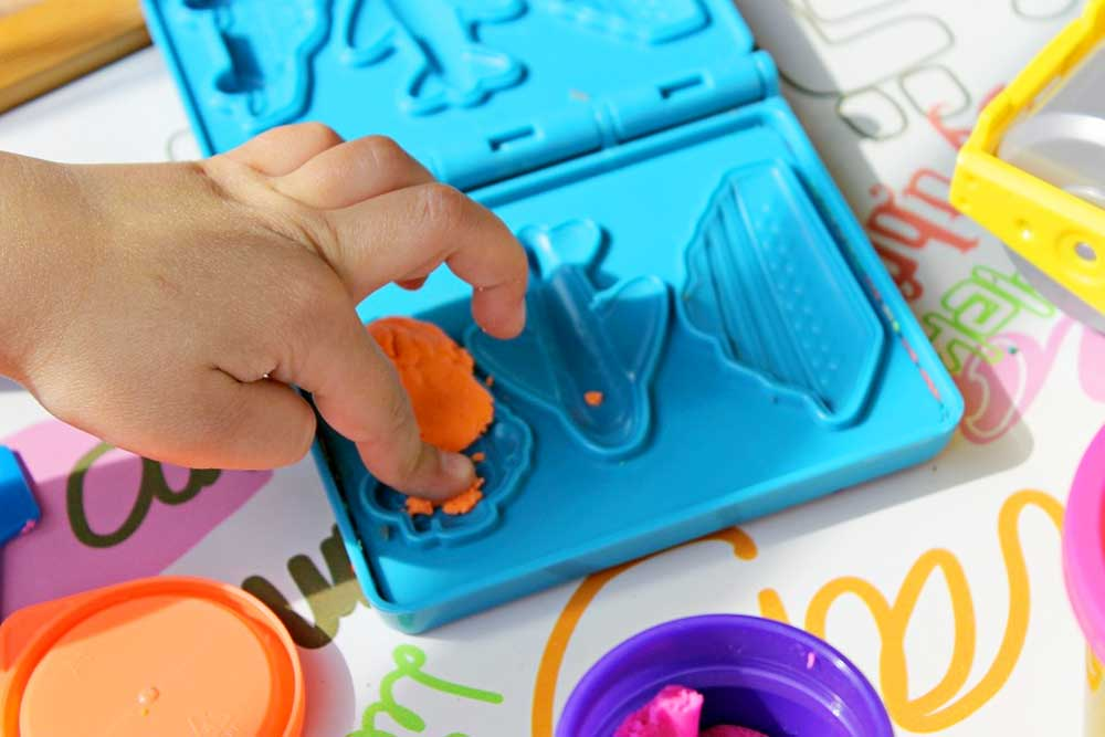 Child's hand pressing orange play-doh into a blue mold with spaces to make a car, plane, or cruise ship.