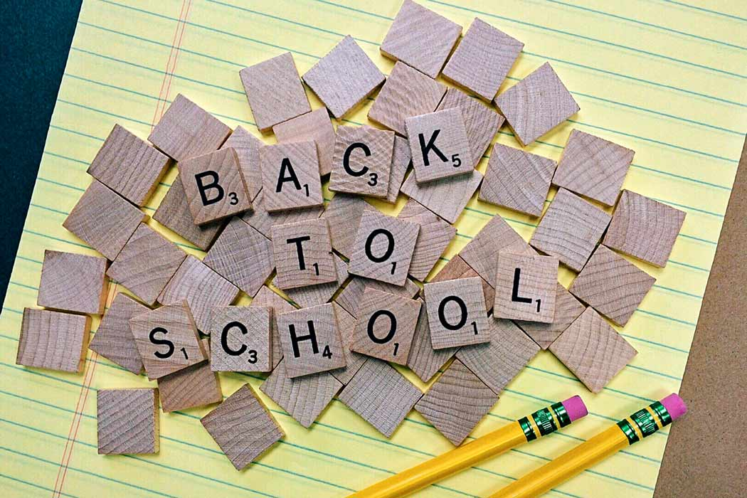 back to school scrabble tiles on lined paper with pencils