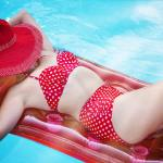 Woman on a pool float in a red bikini