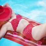 Woman on a pool float in a red bikini