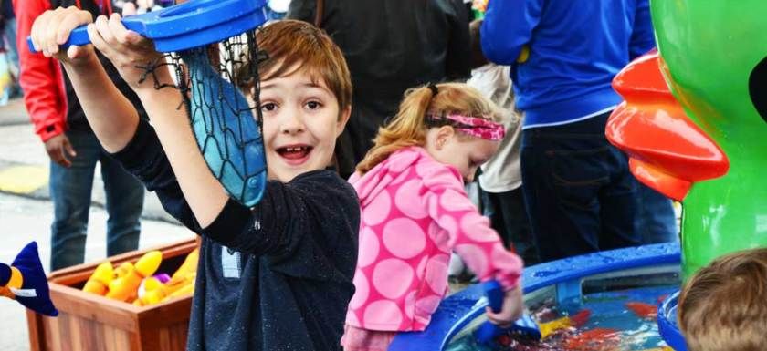 Little boy holding up a blue plastic fish in a net he caught for a carnival game