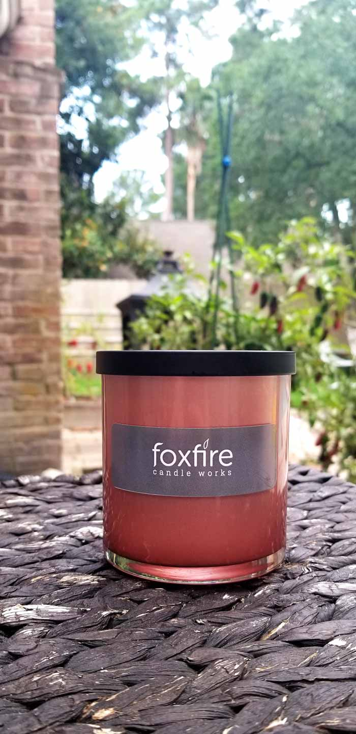 White soy candle in glass rose gold container with foxfire candle works label sitting in front of a raised garden bed.