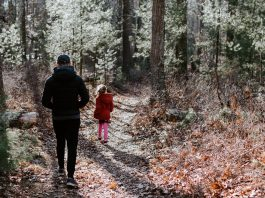 man and girl walk on wooded trail